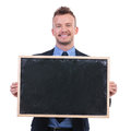 Business man holds a blackboard young holding in his hands and smiling to the camera on white background Royalty Free Stock Photography
