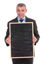Business man holds a blank blackboard holding in his hands while looking into the camera on white background Royalty Free Stock Images
