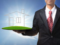 Business man and home on green land in hand for multipurpose Stock Photography