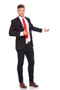 Business man inviting you in the back full length picture of a young presenting way with a smile on his face isolated on Royalty Free Stock Image