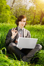 Business man with a laptop on the grass field Stock Photo