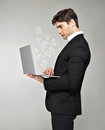 Business man with laptop and mail icon in hand over grey background Royalty Free Stock Image