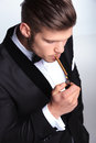 Business man lighting his cigar up closeup picture of an elegant young fashion in tuxedo on gray background Royalty Free Stock Photography