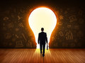 Business man looking at bright light bulb in the wall Royalty Free Stock Photo