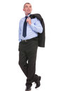 Business man looks away and holds jacket over shoulder full length picture of a holding his his a hand in his pocket while looking Royalty Free Stock Photos