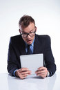 Business man looks surprised at his tablet Stock Photo