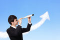 Business man looks through a telescope young against the blue sky with growth arrow cloud symbol of leadership success and Stock Photo