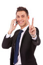 Business man making victory sign on phone Stock Photo