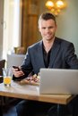 Business man with mobilephone and laptop in portrait of confident sitting restaurant Royalty Free Stock Photos