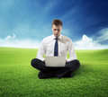 Business man with notebook sitting on grass Royalty Free Stock Images