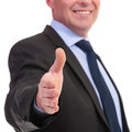 Business man offers hand for shaking closeup of a offering a handshake with a smile on his face on a white background Stock Photos