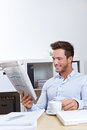 Business man in office reading Stock Images