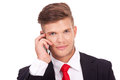 Business man on the phone closeup picture of a young talking and smiling to camera isolated white background Royalty Free Stock Images
