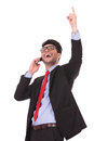 Business man on the phone pointing up Stock Images