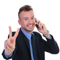 Business man on the phone shows victory young showing sign while white background Stock Image