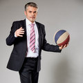 Business man playing with a basketball at the senior businessman getting ready to shoot Stock Images