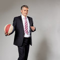 Business man playing with a basketball at the senior businessman getting ready to shoot Royalty Free Stock Photo