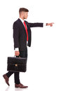 Business man point to side view picture of a young holding a briefcase and pointing while walking forward away from the camera Stock Photos