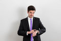 Business man is pointing at his watch and smiling this picture was taken in a studio Royalty Free Stock Image