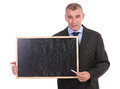 Business man points with chalk on blackboard pointing at a he is holding while looking into the camera a white background Stock Image