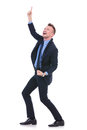 Business man points upwards full length picture of a young pointing and looking with a smile on his face on white background Stock Photos