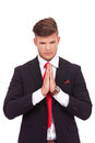 Business man praying young with his hands together and looking down isolated on white background Royalty Free Stock Image