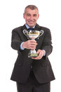 Business man presents his trophy presenting while looking into the camera on a white background Royalty Free Stock Image