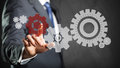 Business man pressing a specific cog wheel to keep the system running Stock Photos