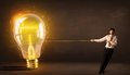 Business man pulling a big bright glowing light bulb Royalty Free Stock Photo