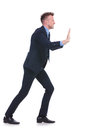 Business man pushes imaginary wall full length picture of a young pushing an to a side on white background Royalty Free Stock Photos