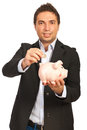 Business man put coin to piggy Stock Photos