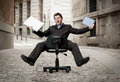 Business man rolling downhill on chair with computer and tablet Royalty Free Stock Photo