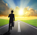 Business man running on asphalt road forward with arrow and beautiful sunset and sunshine concept Stock Image