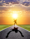 Business man running happily to successful road with sunset
