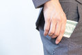 Business man's hand hiding money in pocket Royalty Free Stock Photo