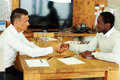 Business man shaking hands with colleague young men across the table Royalty Free Stock Photography