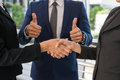 Businessman show thumb up and businesswoman shaking hands for demonstrating their agreement to sign agreement between their firms Royalty Free Stock Photo