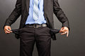 Business man showing his empty pockets on gray background Royalty Free Stock Photos