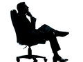 Business man sitting armchair relaxing silhouette Royalty Free Stock Image