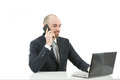Business man sitting at the office and talking on the phone caucasian in front of his laptop Royalty Free Stock Photos