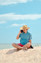 Business man sitting at seaside with tablet computer on call businessman in hat sandy beach and making phone summer sea outdoors Stock Photo