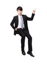 Business man sitting on some thing and show copy space by finger in full length isolated white background asian model Stock Image