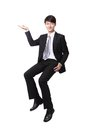 Business man sitting on some thing and show copy space by hand in full length isolated white background asian model Royalty Free Stock Image
