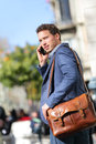 Business man on smart phone barcelona smartphone walking in street talking mobile smiling wearing jacket and leather laptop bag Royalty Free Stock Photo