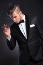 Business man with smoke in his mouth elegant young fashion tuxedo taking a and holding a hand pocket while looking away form the Royalty Free Stock Photo