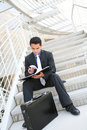 Business Man on Stairs Reviewing Notes Royalty Free Stock Images