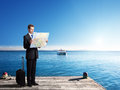 Business man standing on pier with map Royalty Free Stock Photo