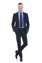 Business man stands with both hands in pockets full length picture of a young standing legs crossed and his while smiling at the Royalty Free Stock Photo