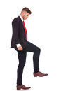 Business man stepping on something full length picture of a young imaginary and looking at it isolated white background Royalty Free Stock Photography