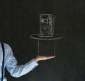 Business man student or teacher pulling money from a magic hat on blackboard background Stock Photo